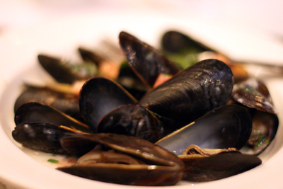 The mussels are served in a sauce that is perfect for bread dipping.