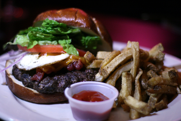 Kuma's famous burger is topped with bacon and a fried egg -- breakfast on a burger!