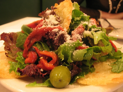 The house salad is wonderful, served with peppers, olives, and fresh Parmesan cheese.